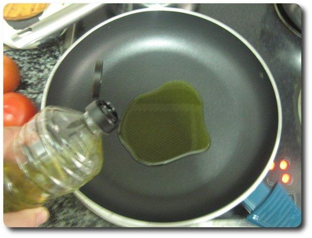 En una sartén amplia, esta es de 28 cm., echamos unas 4 cucharadas de aceite de oliva virgen extra. Lo ponemos a fuego medio.