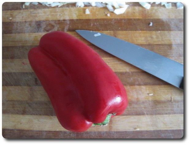 Vamos a cortar un pimiento. Puede usarse tanto verde como rojo, pero a mí me gusta más usar el rojo en esta receta pues, y aunque echaremos pimentón luego, contribuye a darle un mejor color rojizo al plato.