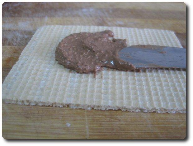 Una vez que tengamos bien mezclado el chocolate fundido con el polvo de avellanas y azúcar glass, lo vamos extendiendo sobre unas obleas de las de los helados de corte.