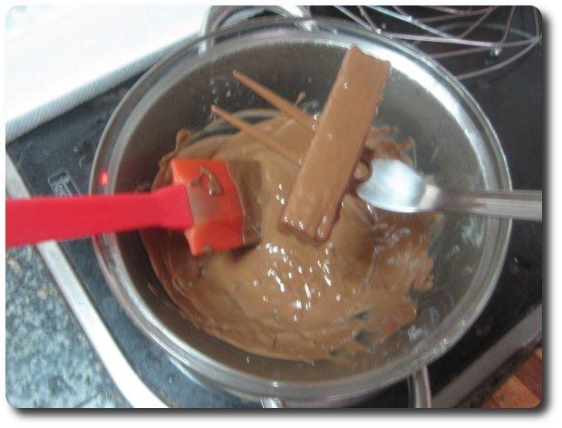 Lo empapamos bien de chocolate por todas sus partes. Para sacarlo podemos emplear un tenedor, por ejemplo, pero, al tener los dientes muy juntos no va a escurrir bien el chocolate restante. Yo empleo un pincho de los de la carne doblado en L. Le damos unos golpecitos para que se caiga lo que sobra y ya está listo para sacar.