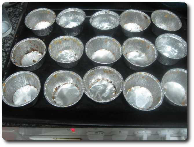 Encendemos el horno a 250º C. Yo empleo unas flaneras de aluminio para contener los moldes de papel de las magdalenas, y así no se me abren y se mantienen más erguidas. Los moldes se usan un montón de veces.