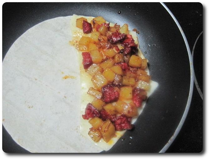Por encima del queso vamos a echar una porción del sofrito de patata, cebolla y chorizo.