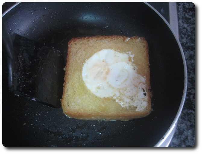 Lo desplazamos suavemente por la superficie de la sartén, para que tome la mantequilla que queda derretida en la misma. El tiempo que lo tengamos aquí nos dará el resultado final. Si nos quedamos cortos, al querer comer nuestra tostada será todo huevo líquido. Si nos pasamos de tiempo, nos quedará la yema totalmente dura, como cocida. En mi caso lo tuve así 1 minuto a la potencia de la vitro que antes comenté. Debemos ver que la yema está algo blanda al tacto.