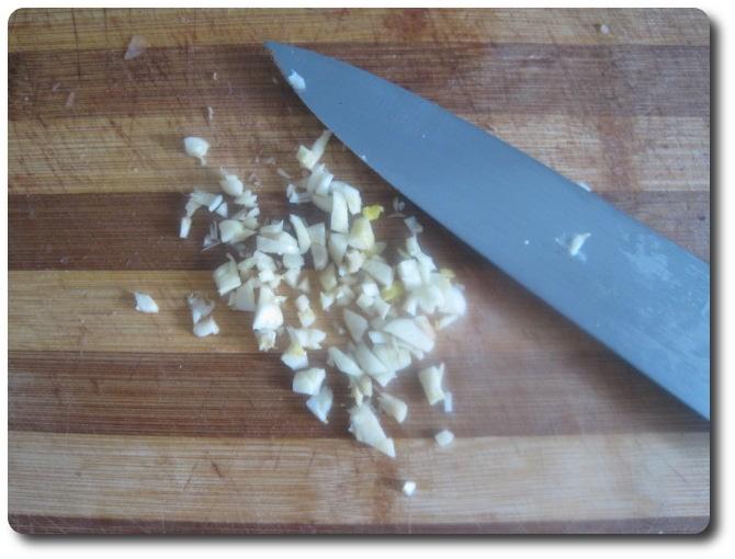 Nos quedará todo picadito. Después de usar el cuchillo para cortar ajo nunca debemos limpiarlo con un trapo, ni las manos tampoco. Ponemos todo, cuchillo y manos, bajo un chorro de agua y mojamos un poco. Echamos el ajo picado en el aceite, para que se vaya calentando.