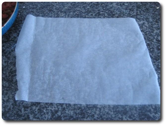 Extendemos otro trozo de papel de hornear, del ancho de la bandeja, sobre la mesa de trabajo.
